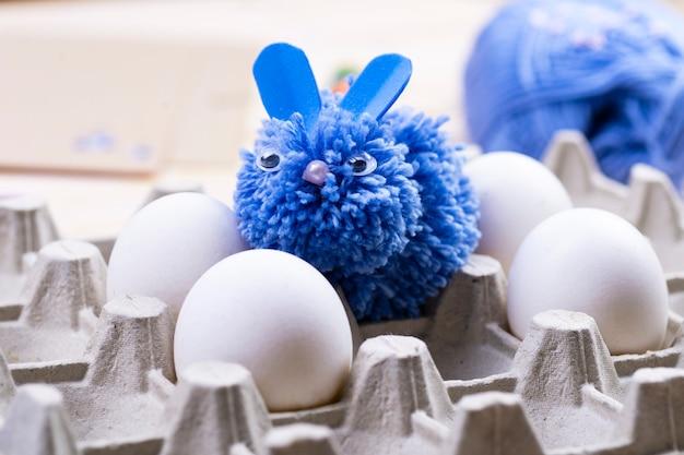 Dit blauwe konijn is met de hand gemaakt van pom-poms voor paasdecoratie. paashaas en witte eieren op een standaard