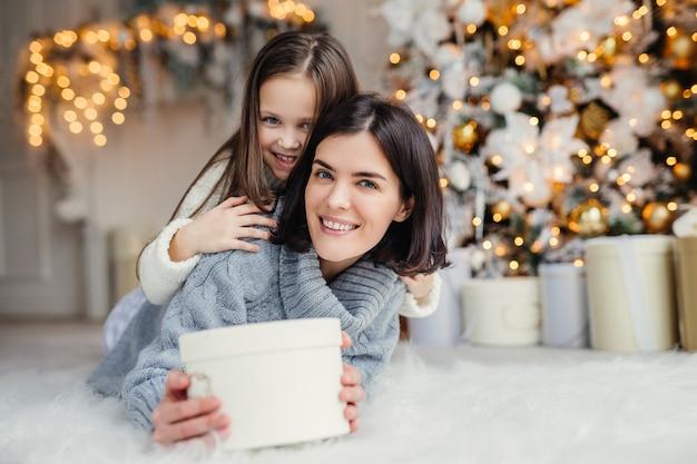 Dit cadeau is voor jou! gelukkig klein kind omhelst haar aanhankelijke moeder die verpakt verpakt houdt