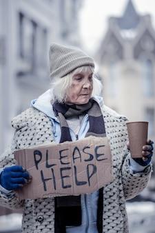 Dit is armoede. ongelukkige ongezellige vrouw die op straat staat terwijl ze in de beker met munten kijkt