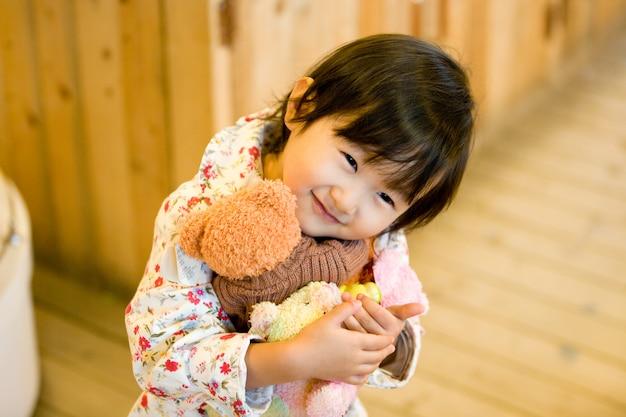 Dit is een kind dat een teddybeer knuffelt en gelukkig is