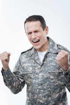 Dit is een mislukking. depressieve knappe militaire man die tegen de achtergrond staat en zijn emoties toont terwijl hij van streek is door de mislukking