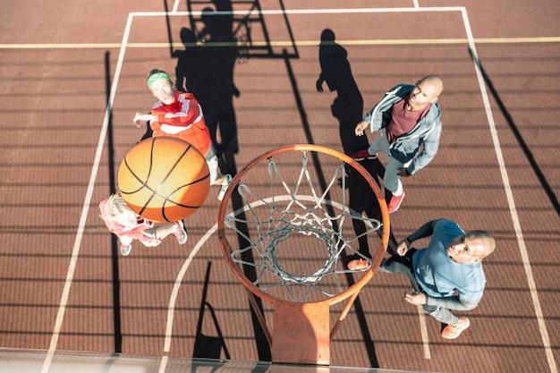 Dit is een partituur. bovenaanzicht van een bal die in de mand vliegt tijdens het spelen van een basketbalspel