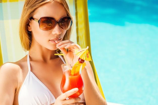 Dit is het echte leven! mooie jonge vrouw in witte bikini cocktail drinken terwijl u ontspant in de ligstoel bij het zwembad