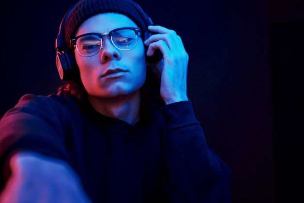 Dit is mijn favoriete liedje. studio opname in donkere studio met neonlicht. portret van ernstige man