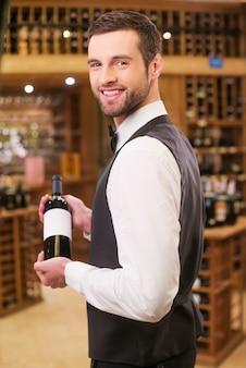 Dit is onze beste wijn. zelfverzekerde jonge man in vest en vlinderdas die fles met wijn vasthoudt en over de schouder kijkt terwijl hij in de slijterij staat