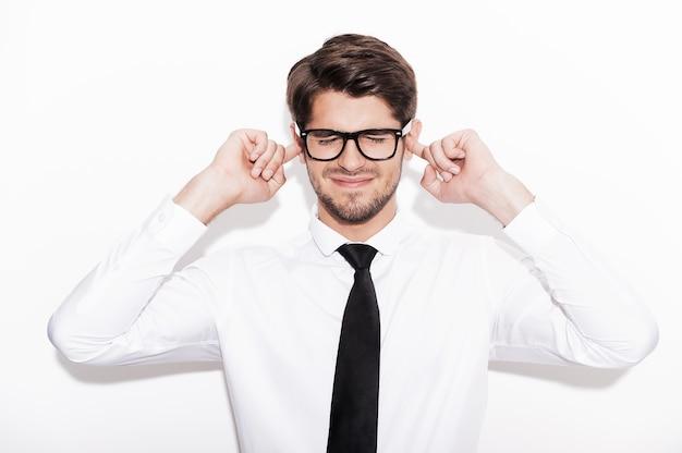 Dit is te luid! gefrustreerde jonge man die vingers in de oren houdt en de ogen gesloten houdt terwijl hij tegen een witte achtergrond staat