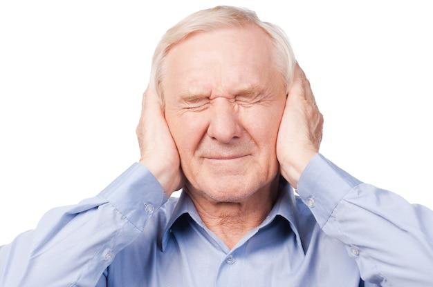 Dit is te luid! gefrustreerde senior man in shirt met hoofd in handen en ogen gesloten terwijl hij tegen een witte achtergrond staat