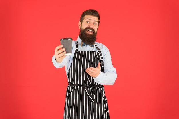 Dit is voor jou. bebaarde man houdt koffie mee. brutale ober in café. volwassen man rode achtergrond. geschoolde dienaar. barista hipster chef-kok schort. elegante zelfverzekerde barman. man drinkt koffie.