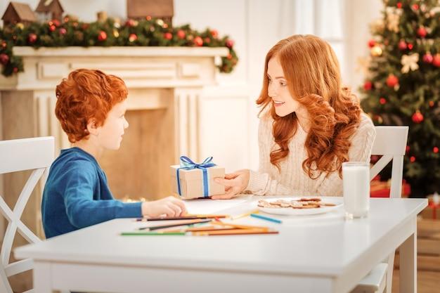 Dit is voor jou. selectieve aandacht voor een volwassen dame die lacht terwijl ze naast haar verbaasde zoon zit en hem thuis een klein kerstcadeautje geeft.