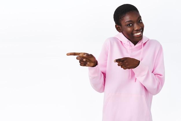 Dit moet je zien. schattige lachende afro-amerikaanse vrouw met kort kapsel, wijzende vingers naar links naar lege witte ruimte, aanbevelen klik op link