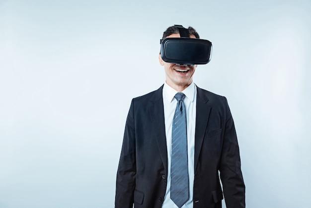 Dit ziet er zo echt uit. taille-up shot van een opgewonden kantoormedewerker die een zwart pak draagt en een virtual reality-headset probeert over de lichte achtergrond.