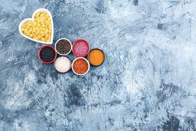 Ditalini pasta in een witte kom met kruiden bovenaanzicht op een grijze gips achtergrond
