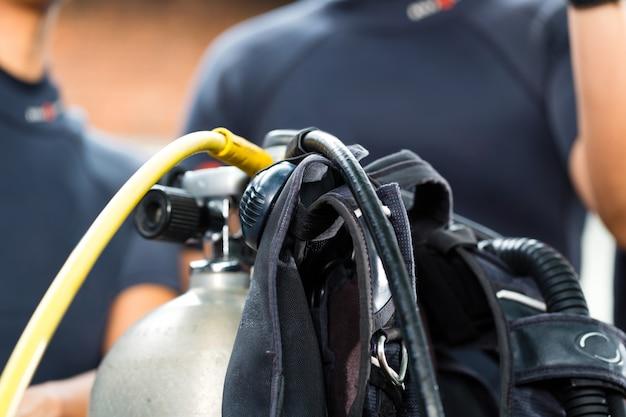 Divemaster en studenten bij de duiker cursus op vakantie in een wetsuit of duiken op de voorgrond is een zuurstoftank