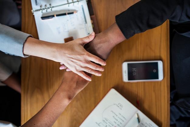 Divers commercieel team dat handen stapelt