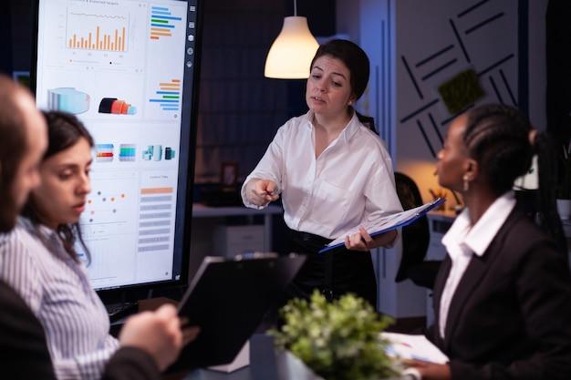 Divers multi-etnisch zakelijk teamwerk dat overwerkt in kantoorvergaderruimte die 's avonds laat financiële grafieken analyseert