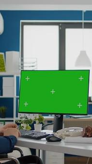 Divers team dat samenwerkt met financiële grafieken die kijken naar groen scherm, mock-up, chroma key izolated desktop, zwarte vrouw en verlamde collega in rolstoel die oplossing voor project bespreekt