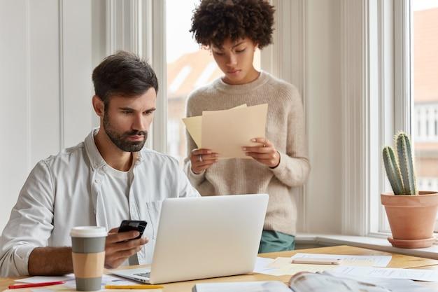 Divers team van medewerkers heeft informele bijeenkomst in huiselijke sfeer, werkt met papieren documenten, ontwikkelt startup tijdens briefing. gerichte serieuze mannelijke ceo houdt gsm controleert e-mailbox op laptop