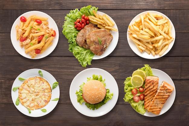 Divers voedsel dat op de houten achtergrond wordt geplaatst