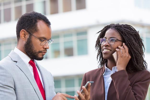 Divers zakenlui die mobiele telefoons gebruiken