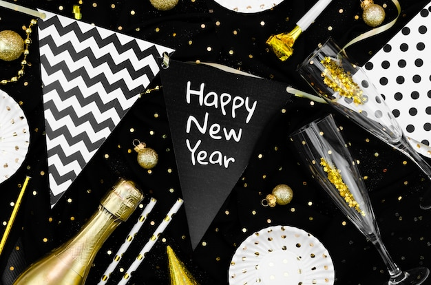 Diverse accessoires en glazen op zwarte achtergrond en gelukkige nieuwe jaarslinger