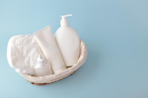 Diverse accessoires voor kinderhygiëne. luiers en flessen babycosmetica in de mand. copyspace