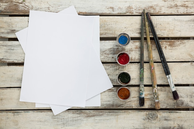 Diverse aquarelverf, papier en penselen op houten oppervlak