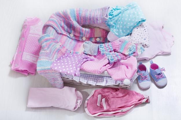 Diverse babykleding in een doos op houten tafel, bovenaanzicht