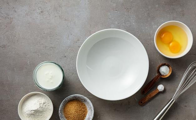 Diverse bakingrediënten en lege kom op keukentafel, bovenaanzicht