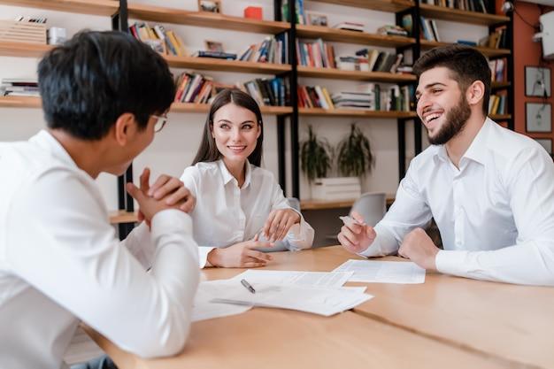 Diverse bedrijfsmensen in het bureau die en het werk glimlachen bespreken