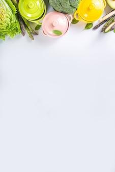 Diverse biologische groene lente plantaardige ingrediënten met lege kleurrijke geportioneerde kookpotten op witte keukentafel, bovenaanzicht. dieet gezonde soep, stoofpot voedselbereiding concept