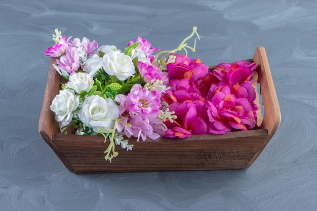 Diverse bloemen in een doos, op de witte tafel.