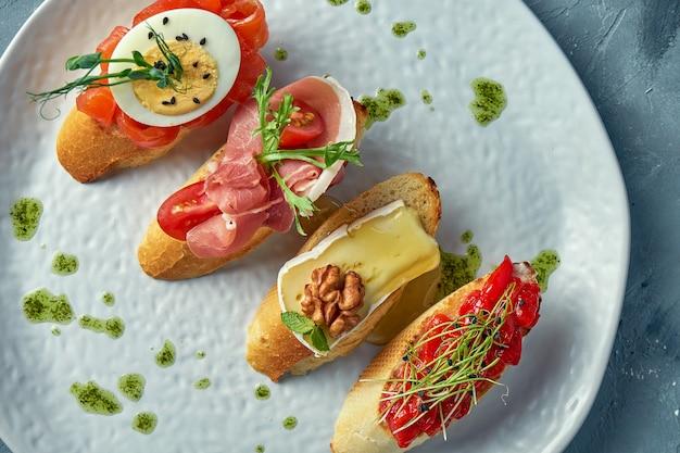 Diverse bruschetta met gebakken paprika, camembert, prosciutto en licht gezouten zalm in een witte plaat