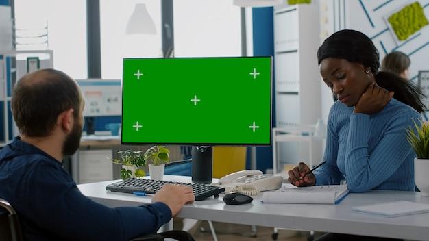 Diverse businessteam controleren met financiële grafieken kijken naar groen scherm