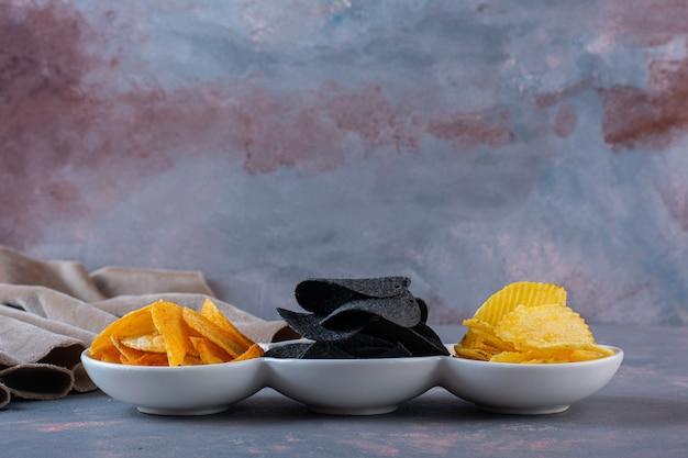 Diverse chips in een kom op het marmeren oppervlak