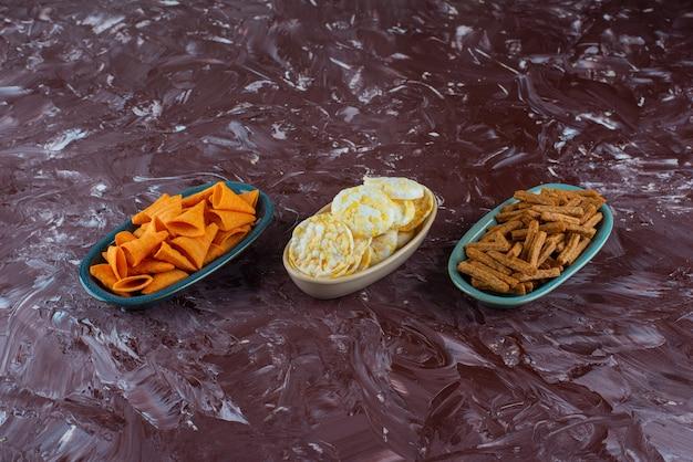 Diverse chips in kommen, op de marmeren tafel.