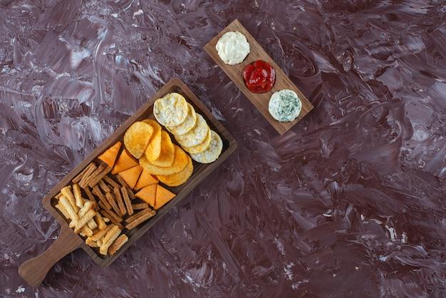 Diverse chips op serveerplank met saus, op de marmeren tafel.