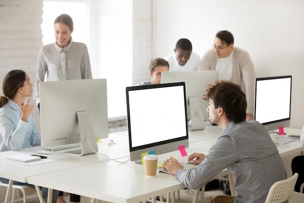 Diverse collectieve werknemersgroep die werkt samen gebruikend computers in bureau