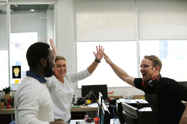 Diverse collega's met high five