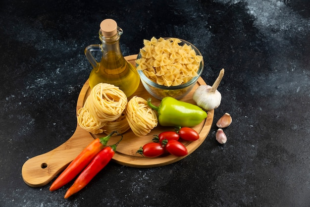 Diverse deegwaren, olie en groenten op houten raad.