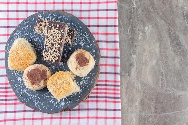 Diverse desserts op een bord op theedoek op marmer.