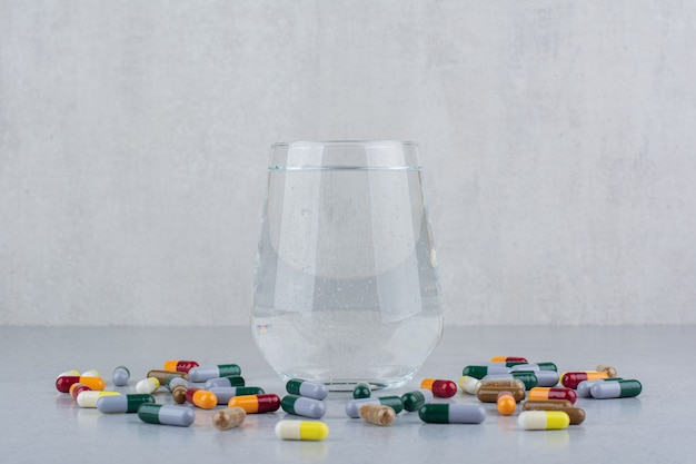 Diverse farmaceutische capsules en glas water.