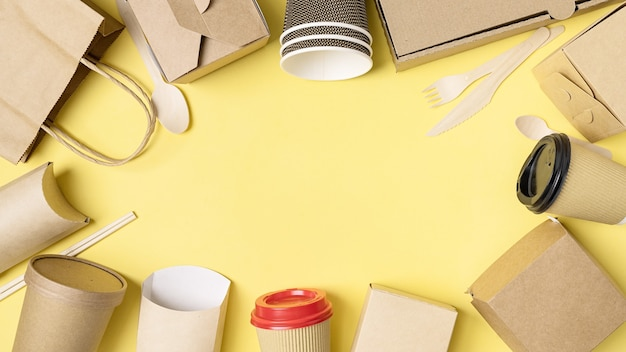 Diverse fast food verpakkingen ingesteld op gele achtergrond. maaltijdbezorgservice. bovenaanzicht. ruimte kopiëren.