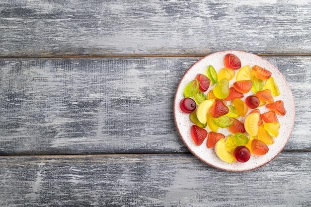 Diverse fruit gelei snoepjes op plaat op grijze houten achtergrond
