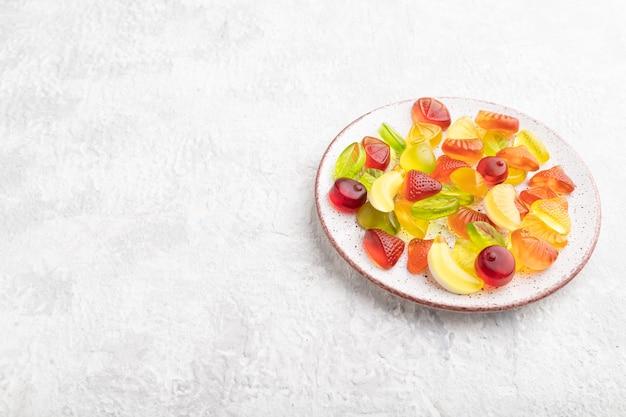 Diverse fruitgelei snoepjes op plaat op grijze betonnen achtergrond