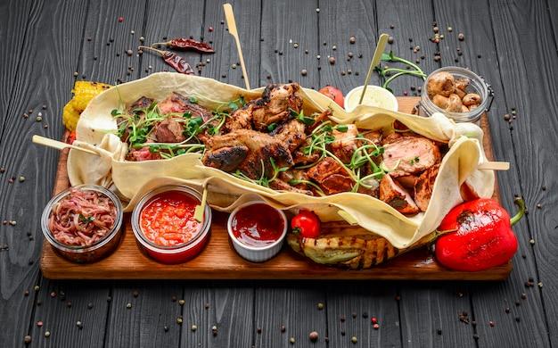 Diverse gebakken gegrilde vleessnacks met diverse sauzen