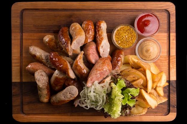 Diverse gebakken worstjes, met gebakken aardappelen, sla, zilveruitjes en sauzen, mosterd, ketchup en franse mosterd, op een houten plank, op zwarte ondergrond