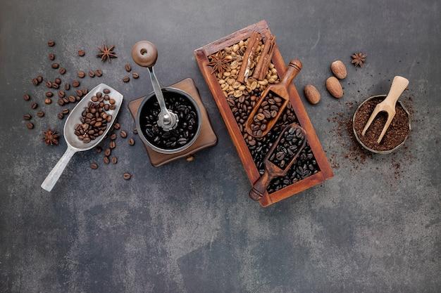 Diverse gebrande koffiebonen in houten doos met handmatige koffiemolen setup op donkere steen.