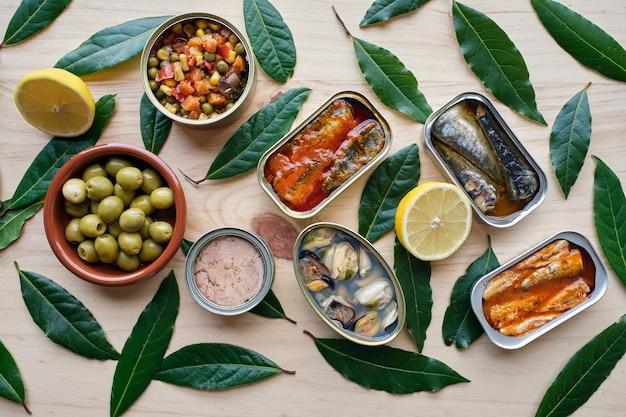 Diverse geconserveerde groenten en vis, citroen en olijven. op houten sokkel.