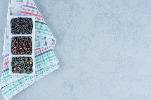 Diverse gedroogde bladeren in de kom op handdoek op marmer.