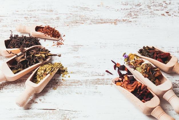 Diverse gedroogde thee in houten bolletjes op witte armoedige tafel